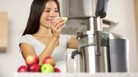 készítő : Woman making apple and vegetable juice on juicer machine at home in kitchen. Juicing and healthy eating happy woman making green vegetable and fruit juice. Mixed race Asian Caucasian model. Stock mozgókép