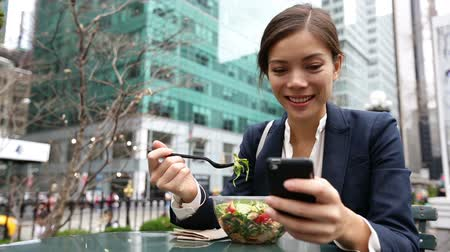 étkezik : Young business woman eating salad on lunch break in City Park living healthy lifestyle working on smart phone. Happy smiling multiracial young businesswoman, Bryant Park, Manhattan, New York City, USA