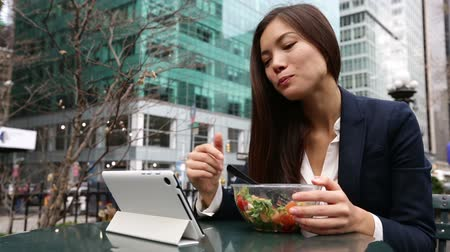 ebéd : Business woman using tablet computer pc eating salad on lunch break in City Park living healthy lifestyle. Happy smiling mixed Asian young businesswoman, Bryant Park, Manhattan, New York City, USA