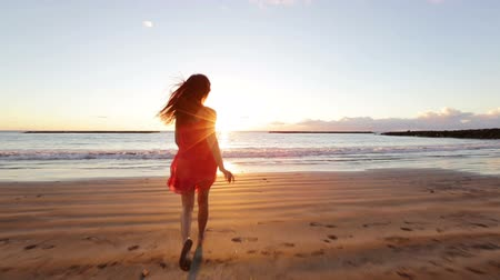 Summer woman beach freedom happy concept. Young woman running towards ocean in dress at sunset with arms stretched free during holidays vacation travel. Beautiful free mixed race Asian Caucasian girl Стоковые видеозаписи