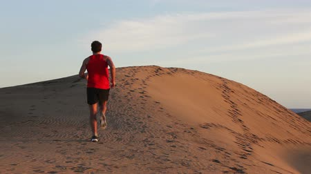 corrida : Male runner running up a hill sand dune in desert. Back view of fit athletic male fitness model training. Sport in amazing extreme desert landscape nature at sunset with jogging male athlete.