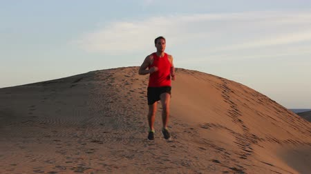 buty sportowe : Athlete runner running in sand dune in desert. Front view of fit athletic male fitness model training. Sport in amazing extreme desert landscape nature at sunset with jogging male athlete.