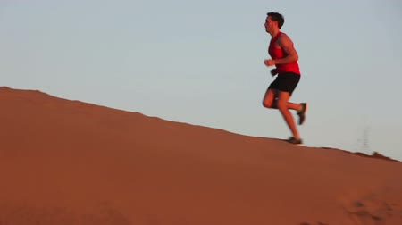 дюна : Runner man running up a hill sand dune in desert. Fit athletic male fitness model training. Sport in amazing extreme desert landscape nature at sunset with jogging male athlete.