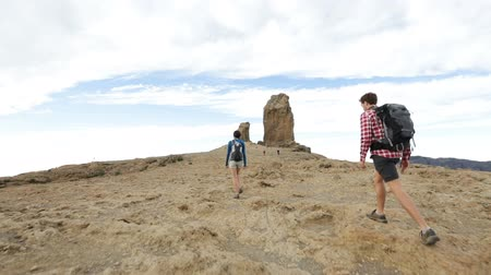 peak : Hikers reaching summit top after ascent. Hiking couple walking outdoors wearing hiker backpacks. Woman and man hiker on trail to Roque Nublo, Gran Canaria, Canary Islands, Spain.