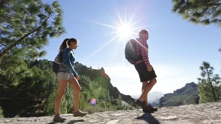 estilo de vida saudável : Hiking couple walking on trail. Healthy lifestyle hiker people walking in mountains. Young woman and man hikers on path to Roque Nublo, Gran Canaria, Canary Islands, Spain.