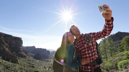 öz : Selfie - couple taking self portrait photo with smartphone hiking. Smiling couple taking self-portrait picture on hike in mountains. Young woman and man hikers on Gran Canaria, Canary Islands, Spain. Stok Video