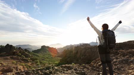 Happy free cheering enjoying freedom hiking celebrating in nature. Hiking woman hiker raising arms excited in celebration by Roque Nublo, Gran Canaria, Canary Islands, Spain.