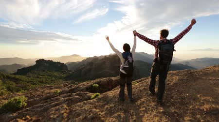 kutluyor : Happy couple cheering and running in nature. Hiking man and woman raising arms excited in celebration outdoors. Hikers cheerful at sunset in mountain by Roque Nublo, Gran Canaria, Canary Islands
