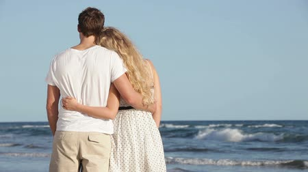 медовый месяц : Romantic lovers couple at beach enjoying honeymoon embracing and looking at ocean sea view. Man and woman in love on travel vacation holidays. Стоковые видеозаписи