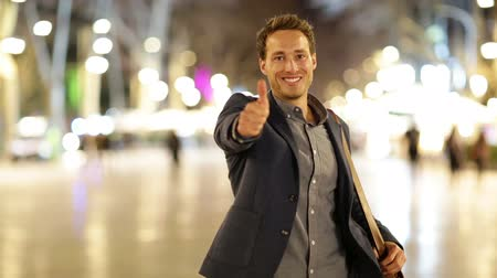 Business man giving thumbs up success hand sign. Happy smiling casual businessman walking into focus smiling happy and successful at night on La Rambla, Barcelona, Spain. Young casual professional man Стоковые видеозаписи