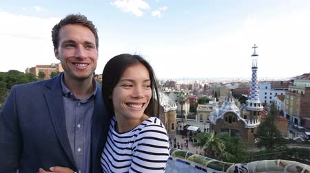 gözlerden uzak : Happy travel couple in Park Guell, Barcelona, Spain. Beautiful young multiracial couple looking away smiling happy having fun on Europe vacation trip. Asian woman, Caucasian man.