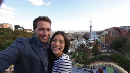 Барселона : Happy couple selfie self portrait photo in Park Guell, Barcelona, Spain. Beautiful young multiracial couple looking at camera having fun on Europe travel vacation. Asian woman, Caucasian man. Стоковые видеозаписи