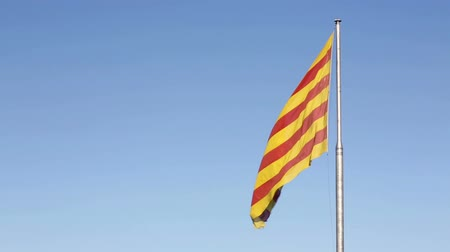 Каталония : Catalan flag in Catalonia, Barcelona, Spain waving against blue sky. Стоковые видеозаписи