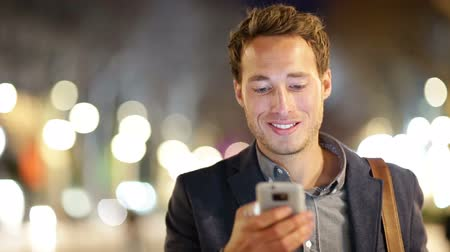 использование : Man sms texting using app on smart phone at night in city. Handsome young business man using smartphone smiling happy wearing suit jacket outdoors. Urban male professional in his 20s.