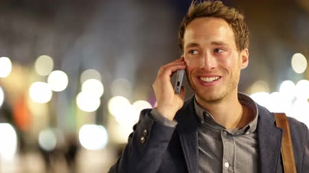telefones : Smart phone man calling on mobile phone at night in city. Handsome young business man talking on smartphone smiling happy wearing suit jacket outdoors. Urban male professional in his 20s.