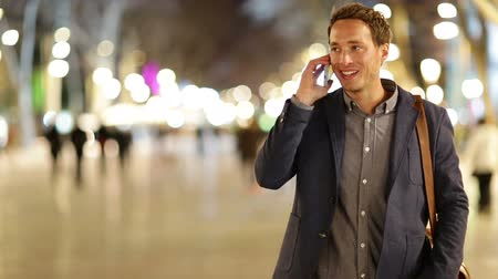 telefone celular : Smart phone man calling on mobile phone at night on La Rambla in Barcelona, Spain. Handsome young business man talking on smartphone and walking away smiling happy wearing suit jacket outdoors.