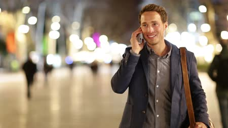 mluvení : Smart phone man calling on mobile phone at night on La Rambla in Barcelona, Spain. Handsome young business man talking on smartphone and walking away smiling happy wearing suit jacket outdoors.