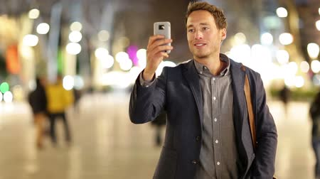 obrázky : Man taking photo with camera phone at night on La Rambla, Barcelona, Spain. Young casual man taking picture with camera phone with flash outdoors.
