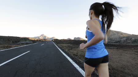 ćwiczenia : Runner woman running on road training for marathon run. Rear view of sporty fit mixed race asian caucasian female fitness sport model working out outside in mountain nature volcano landscape.