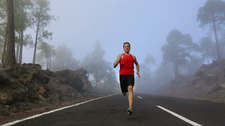 running man : Running sport fitness runner man. Male athlete running and sprinting on mountain road into fog in full body in amazing nature landscape. Fitness model training outdoors for marathon run. Real time. Stock Footage