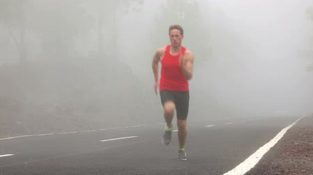 быстрый : Running man sprinting out of fog on mountain road. Runner training sprint run at fast speed outside coming out of the fog. Fit male athlete living active healthy outdoor lifestyle.
