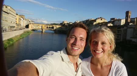 Happy couple selfie photo on travel in Florence. Romantic woman and man in love smiling happy taking self portrait outdoor by Ponte Vecchio during vacation holidays in Florence, Tuscany, Italy, Europe Стоковые видеозаписи