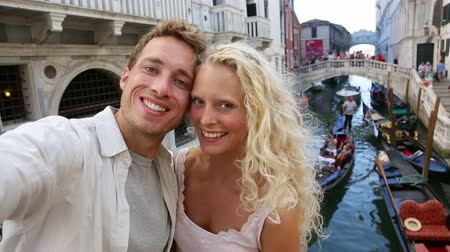 öz : Venice couple taking selfie photo by Canal, Italy on travel together. Young happy couple on holidays or honeymoon having cute romantic vacation in Italy.