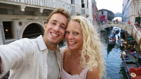 медовый месяц : Venice couple taking selfie photo by Canal, Italy on travel together. Young happy couple on holidays or honeymoon having cute romantic vacation in Italy.