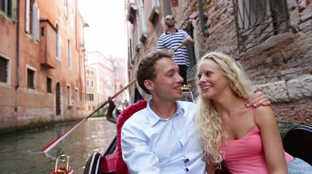 наслаждаясь : Romantic travel couple in Venice on Gondole ride romance in boat talking happy together on travel vacation holidays. Romantic young beautiful couple sailing in venetian canal in gondola. Italy, Europe Стоковые видеозаписи