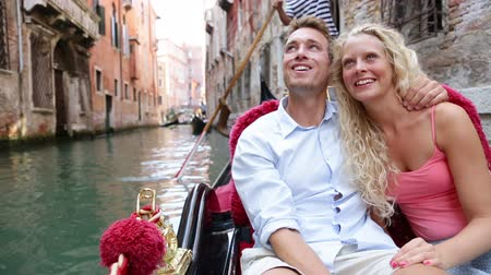 наслаждаться : Travel couple in Venice on Gondola ride enjoying romance in boat happy together on vacation holidays. Romantic young beautiful couple sailing in venetian canal in gondole. Woman pointing. Italy.