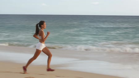 smíšené rasy osoba : Running woman healthy lifestyle jogging on beach. Female runner training exercising outdoors. Happy fit jogger living healthy lifestyle training outside. Fit mixed race Asian Caucasian fitness girl.