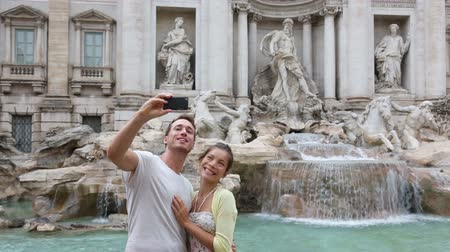 happy : Tourist couple on travel taking selfie photo by Trevi Fountain in Rome, Italy. Happy young romantic couple traveling in Europe taking self-portrait with smartphone camera. Man and woman happy together