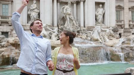 szökőkút : Travel couple throwing coin at Trevi Fountain, Rome, Italy for good luck. Happy young couple smiling traveling together on romantic travel vacation holiday in Europe. Asian woman, Caucasian man.