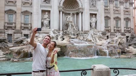 szökőkút : Romantic couple on travel taking selfie photo by Trevi Fountain in Rome, Italy. Happy young tourists couple traveling in Europe taking self-portrait with smartphone camera. Man and woman happy. Stock mozgókép