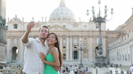 religião : Tourists couple by Vatican city and St. Peters Basilica church in Rome. Happy travel woman and man taking selfie photo picture on romantic honeymoon in Italy.