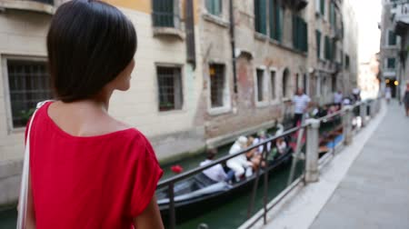 eski moda : Venice, Italy - woman in dress walking by canal in Venice. Elegant tourist girl in her 20s walking showing back rear side. Mixed race Asian Caucasian female model outside.