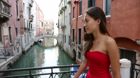brown dress : Venice, Italy - woman in dress walking by canal over bridge smiling in Venice. Tourist girl in her 20s. Mixed race Asian Caucasian female model outside. Stock Footage