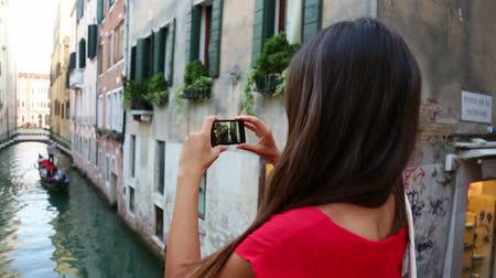 veneza : Woman tourist taking picture photo in Venice, Italy. Travel girl using smartphone taking pictures of canal and gondola during vacation holidays in Europe.