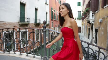 eski moda : Happy beautiful woman in red summer dress walking over canal bridge smiling in Venice, Italy. Pretty sexy fashion model girl in her 20s. Mixed race Asian Caucasian female model outside. Stok Video
