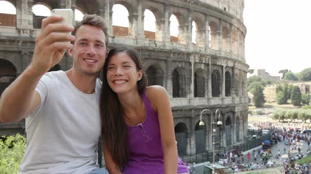 utazó : Tourist couple on travel taking selfie self-portrait pictures by Coliseum in Rome. Happy young romantic couple traveling in Italy, Europe taking photo with smartphone camera in front of Colosseum.