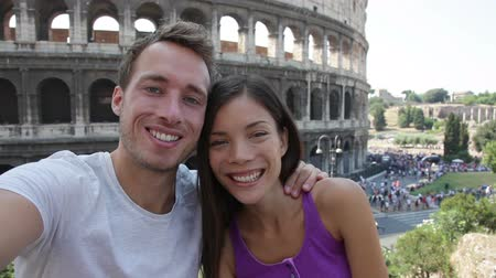 self portrait photography : Selfie - Romantic travel couple by Coliseum, Rome, Italy. Happy lovers on honeymoon sightseeing having fun in front of Colosseum. Woman and man in tourism travel concept.