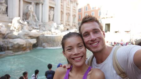 utazó : Tourist couple on travel taking selfie photo by Trevi Fountain in Rome, Italy. Happy young romantic couple traveling in Europe taking self-portrait with smartphone camera. Man and woman happy together