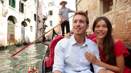 veneza : Romantic travel couple in Venice on Gondola ride romance in boat talking happy together on travel vacation holidays. Young multiracial couple sailing in venetian canal in gondole. Italy, Europe Stock Footage