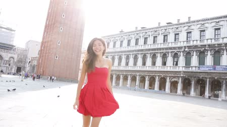 czerwony : Venice woman tourist running playful and fun on San Marco Square, Italy. Smiling happy cheerful multiracial girl elegant in summer dress in Venice. Caucasian Asian model. Wideo