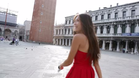 veneza : Venice woman tourist walking on San Marco Square, Italy. Smiling happy cheerful multiracial girl elegant in summer dress on San Marco Square, Venice, Italy. Caucasian Asian model looking at camera.