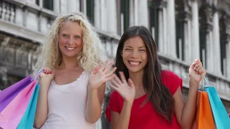 olá : Shopping women waving hands saying hello in Venice holding shopping bags. Portrait of Multiracial girlfriends smiling happy together having fun on San Marco Square, Venice, Italy. Caucasian and Asian.