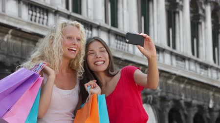 alma : Girlfriends shopping laughing happy taking selfie photo with smartphone. Woman friends holding shopping bags while taking self-portrait picture with smart phone. Blonde girl and Asian woman, 20s