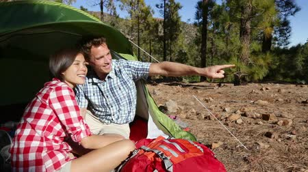 etkinlik : Camping couple in tent laughing and pointing talking looking at view in forest. Campers smiling happy outdoors. Happy people having fun relaxing in outdoor activity. Asian woman, Caucasian man Stok Video