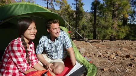 etkinlik : Camping couple in tent sitting looking at view in forest. Campers smiling happy outdoors in forest. Happy multiracial couple having fun relaxing after outdoor activity. Asian woman, Caucasian man.