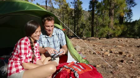 kamp : Camping couple in tent using smartphone looking at pictures photos. Campers smiling happy outdoors in forest. Happy multiracial couple having fun in outdoor activity. Asian woman, Caucasian man Stok Video